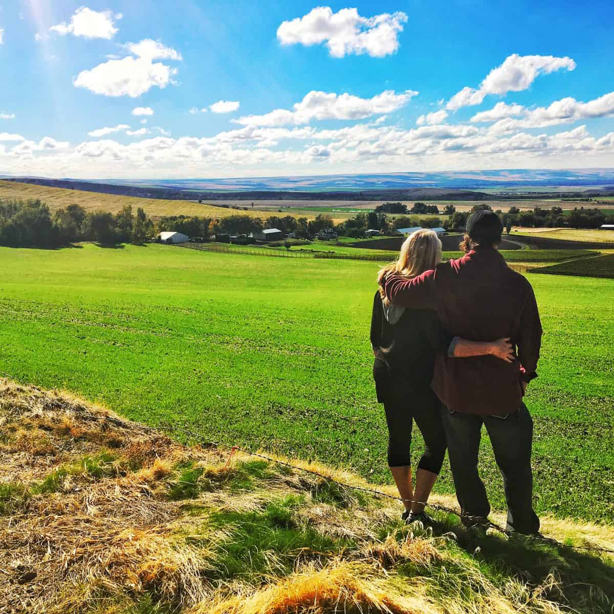 Back of man and woman admiring the view of a green valley after a Walla Walla wine tasting