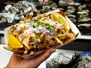 A plate of lobster poutine (fries covered in chunks of lobster, onions and special sauce.,