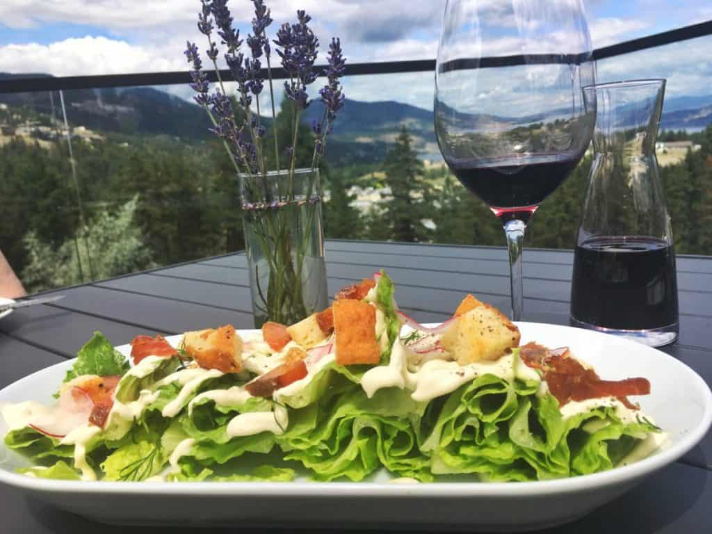 Plate of salad and wine glass at Kelowna Red Fox Club at Indigenous Winery