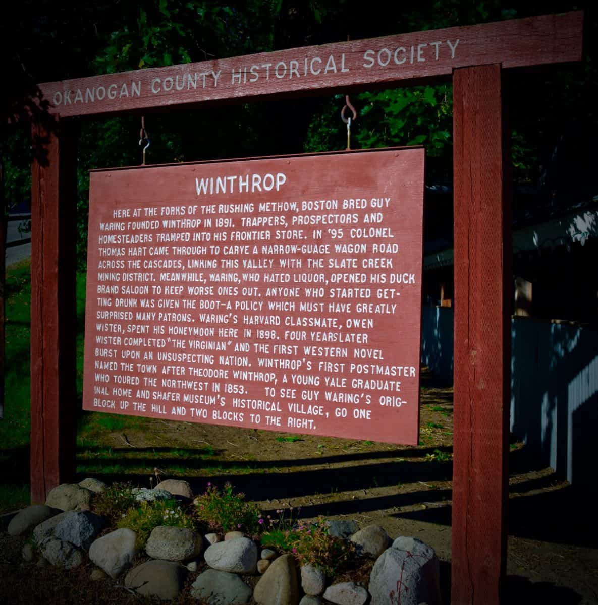 Hanging wooden sign all about the history of Winthrop WA