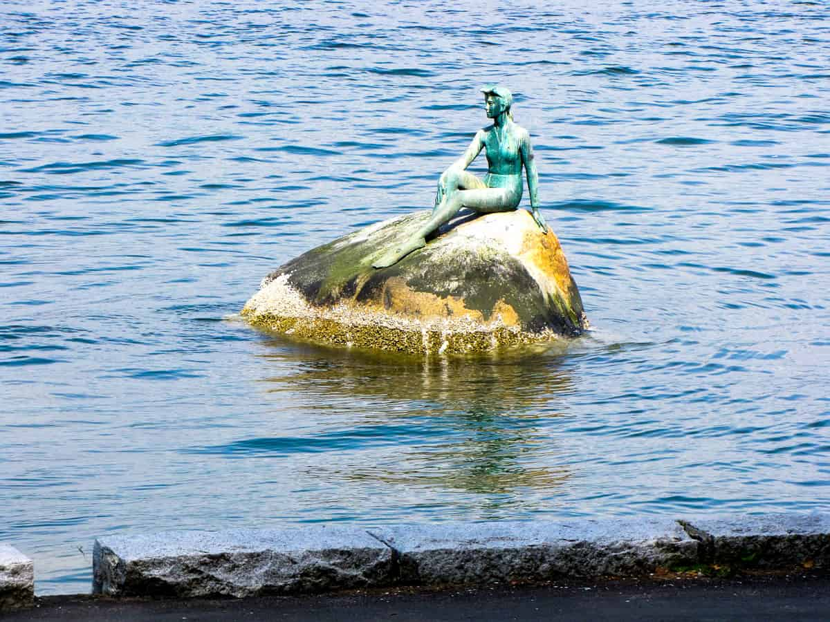Bronze sculpture of a girl in a wetsuit sitting on a rock in the water