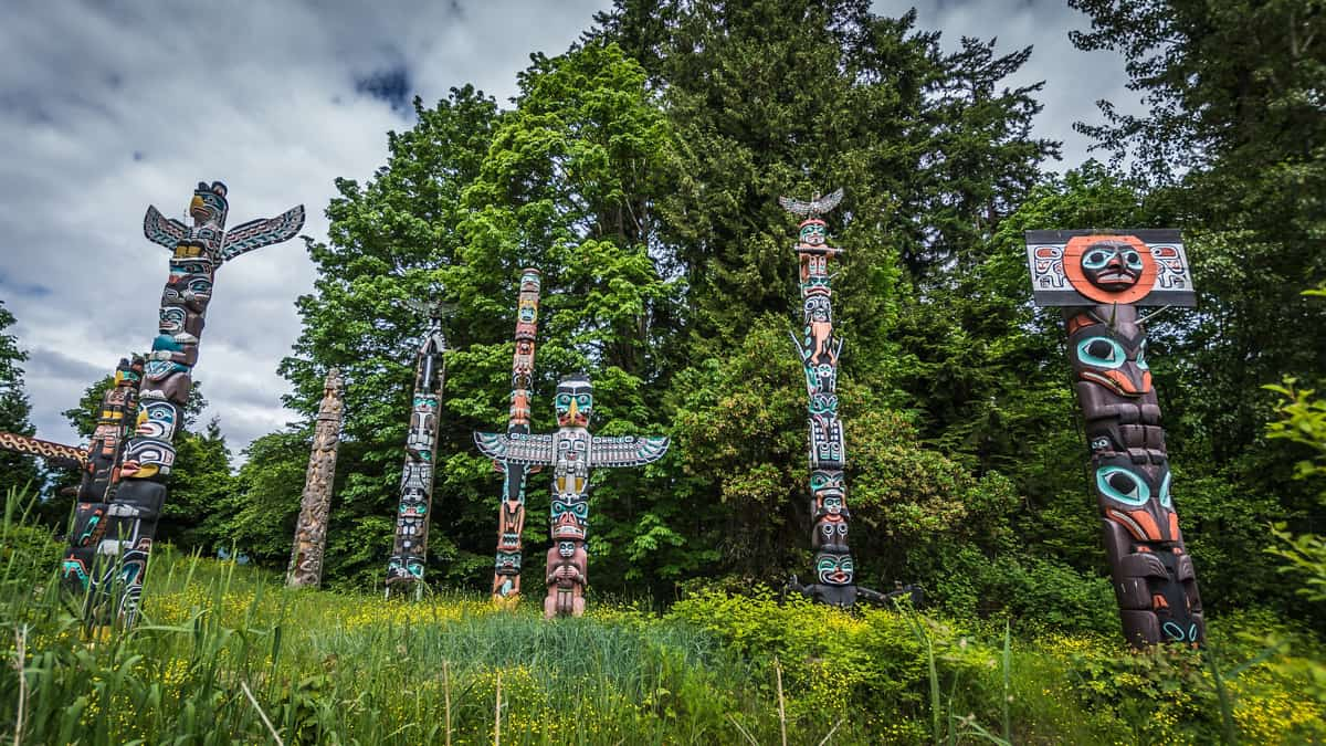 Five Stanley Park Totem Poles backed by green trees