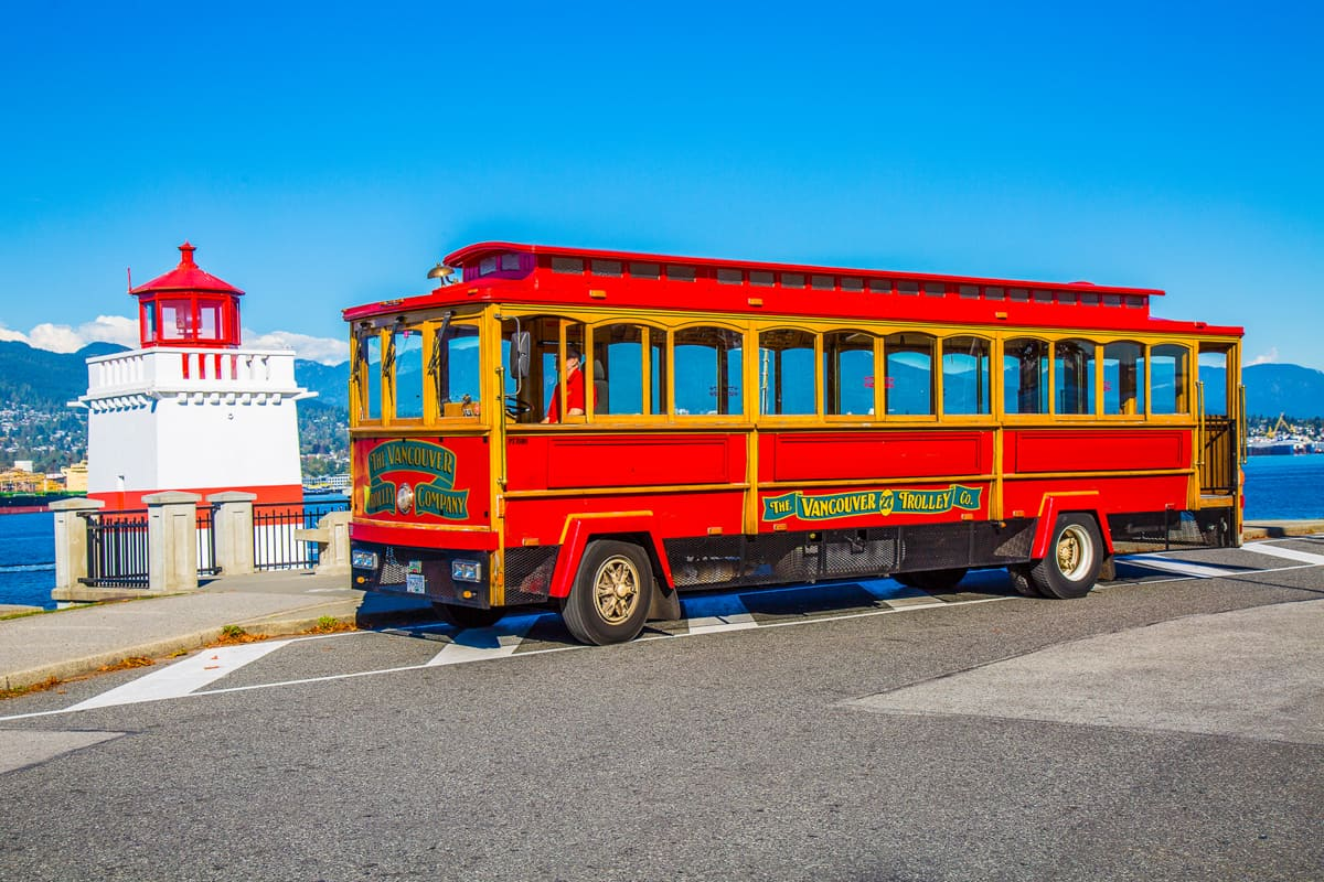 Red trolley sitting in front of a red and white lighthouse