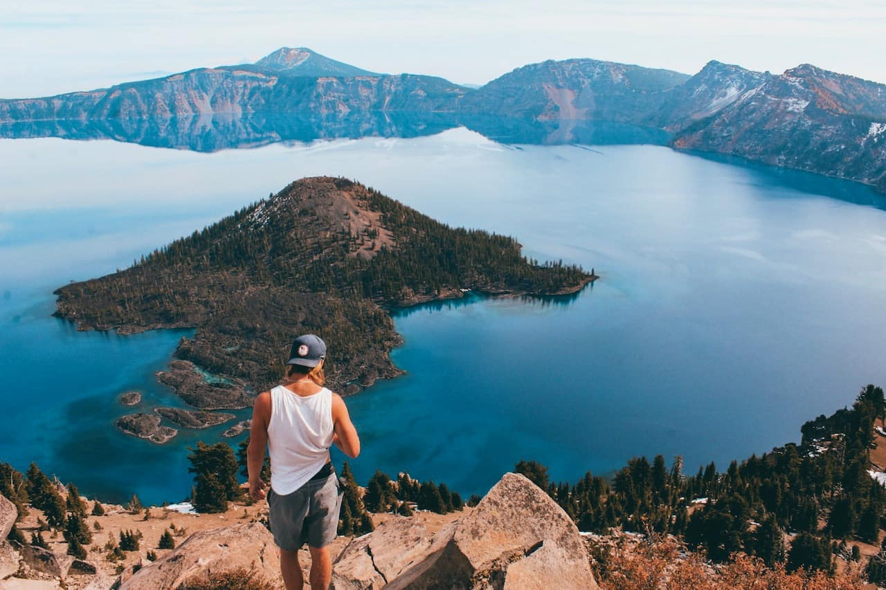 Man looking out an ddown at Crater Lake Oregon