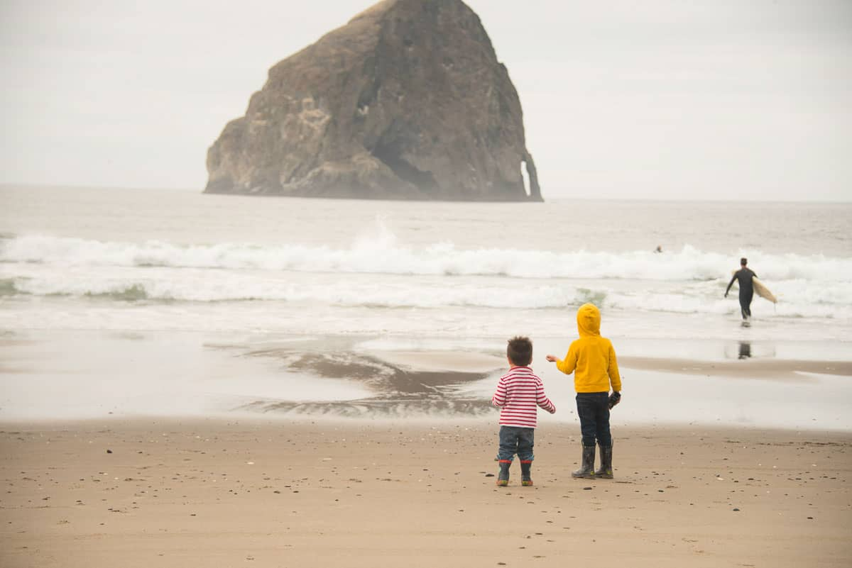 Two small children standing on the beach w looking at a big haystack rock in the background